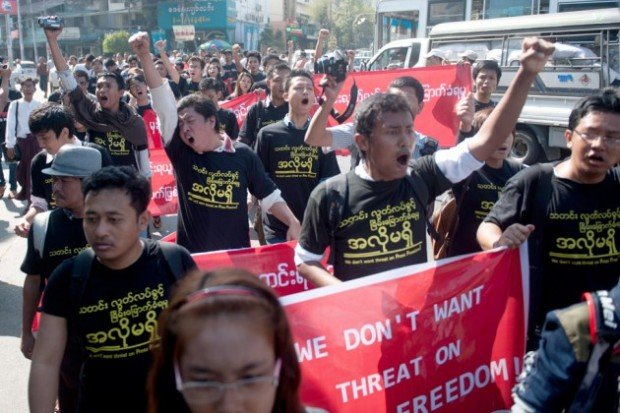 Reporters hold banners and shout slogans as they attend a demonstration march for press freedom in Yangon.